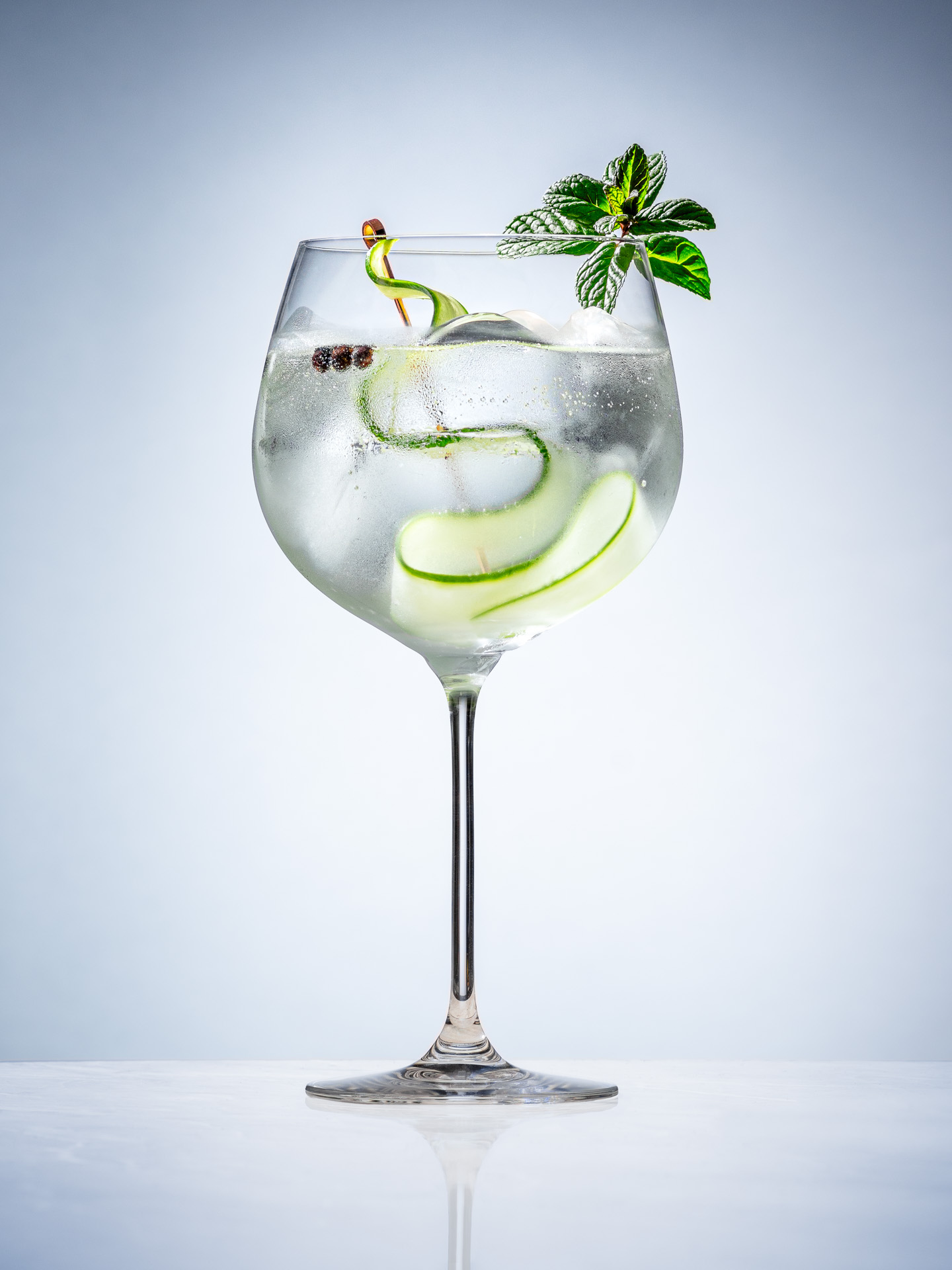 gin and tonic in a tall copa glass garnished with cucamber, juniper berries, and pepermint leaves