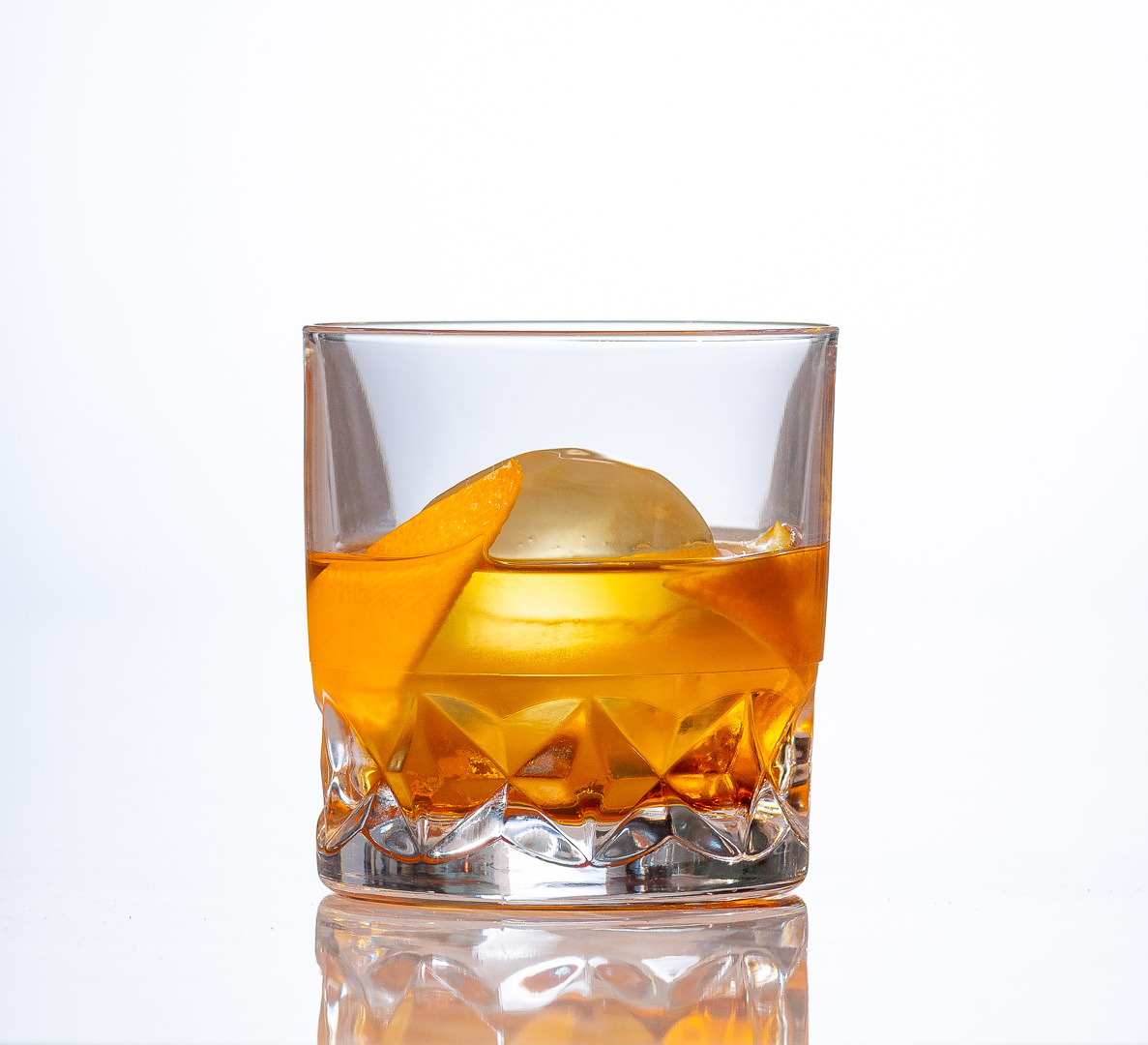 old fashion cocktail with a single spherical piece of ice and garnished with an orange peel